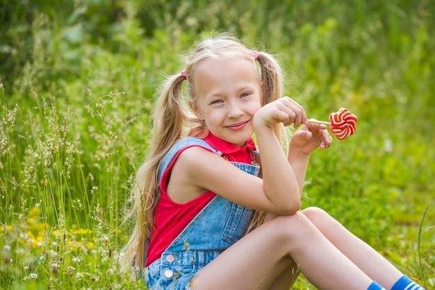長い髪と棒にキャンディと金髪の少女 Premium写真