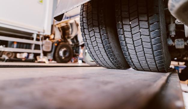 トラックのタイヤのクローズアップ。車のワークショップで古いトラックを修復します。 Premium写真