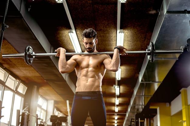 ハンサムな筋肉男がジムでワークアウトします。 Premium写真