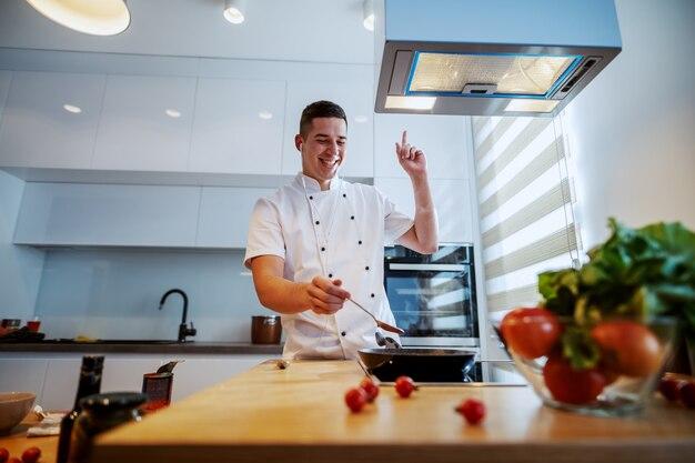 音楽を楽しんでいるとキッチンに立っている間トマトソースを準備する制服を着た陽気な白人シェフ。 Premium写真