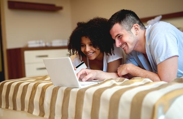 家でのんびり、ノートパソコンを見ているカップル。 Premium写真