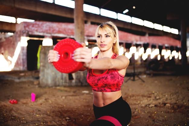 古い格納庫でダンベルでスクワットを行う運動の健康な女性。 Premium写真