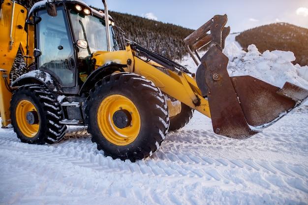 ショベルは森の近くの丘の山で大雪の後の道を切り開きます。 Premium写真