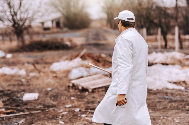 Эколог в белой форме и шапку на голову, проведение буфера обмена во время прогулки на свалке. Premium Фотографии