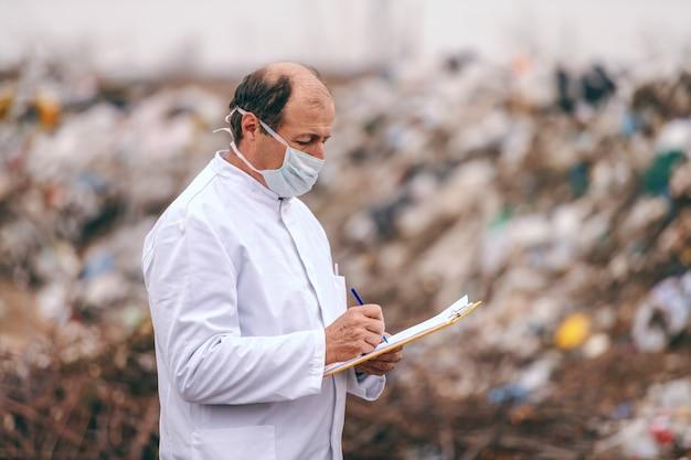 Кавказский эколог в белой форме постоянного записи в буфер обмена результатов и оценки загрязнения на свалке. Premium Фотографии