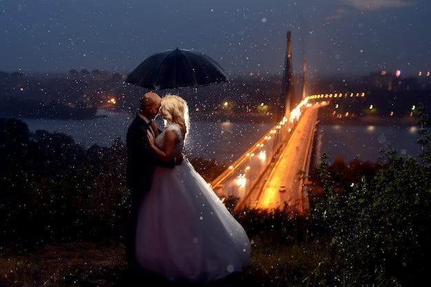 雨の下でキスしたり傘で覆ったりした新婚夫婦 Premium写真