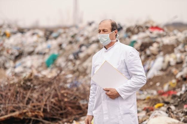 Кавказский эколог в белой форме проведения буфера обмена под мышкой, ходить на свалку и оценки загрязнения. Premium Фотографии