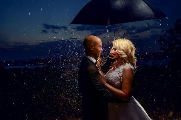 雨の下で傘をさす新婚夫婦 Premium写真