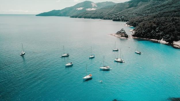 Воздушная выстрел из красивой голубой лагуны в жаркий летний день с парусной лодке. вид сверху. Premium Фотографии