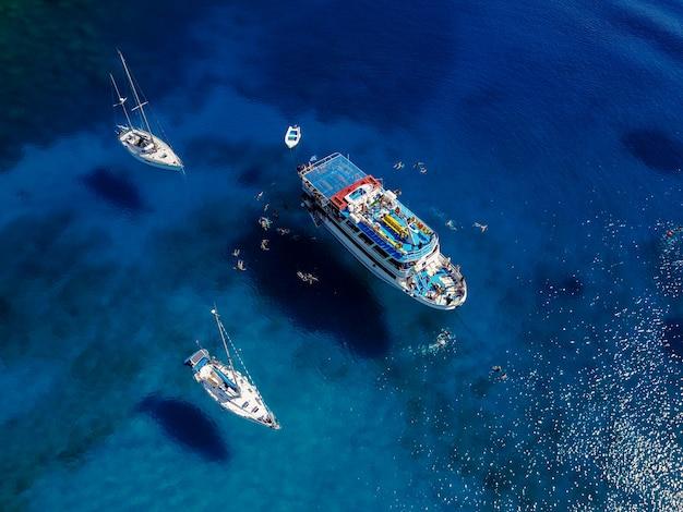 Воздушная выстрел из красивой голубой лагуны в жаркий летний день с парусной лодке. вид сверху людей плавают вокруг лодки. Premium Фотографии