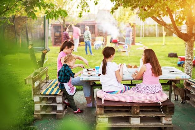 子供たちは木の下のテーブルでピクニックの食事をしている Premium写真