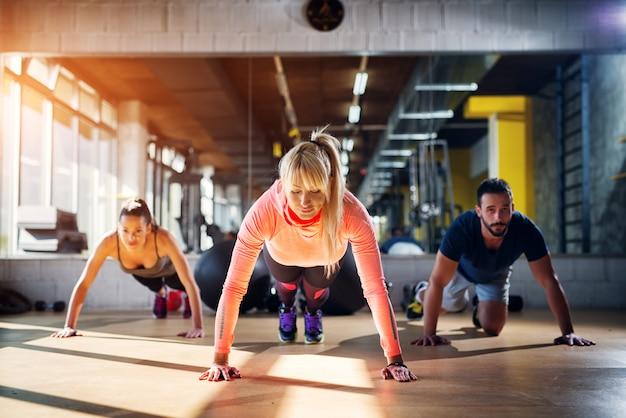 Три сосредоточенных спортивных человека готовят себя к отжиманиям в спортзале. Premium Фотографии