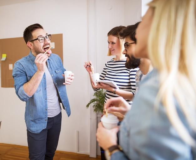 Группа в составе молодые шаловливые счастливые сотрудники имея потеху на проломе пока совместно выпивает кофе в бумажном стаканчике. Premium Фотографии