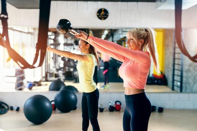 Небольшая группа людей со здоровыми привычками размахивая гири. тренажерный зал интерьер, зеркало в фоновом режиме. Premium Фотографии