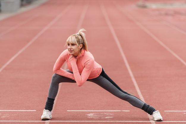 Молодая красивая улыбающаяся белокурая спортивная женщина, растягивающая ногу и нагревающаяся на беговой дорожке перед запуском. Premium Фотографии