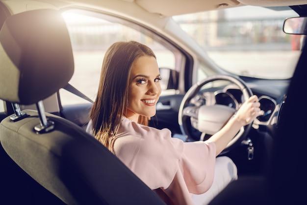 Довольно кавказская брюнетка за рулем автомобиля и глядя на камеру. фото сделано с заднего сиденья. Premium Фотографии