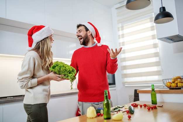 Веселая пара готовит здоровый ужин в канун рождества Premium Фотографии