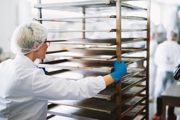 Молодая красивая работница в стерильной одежде толкает стойки с грязными кастрюли для очистки. Premium Фотографии