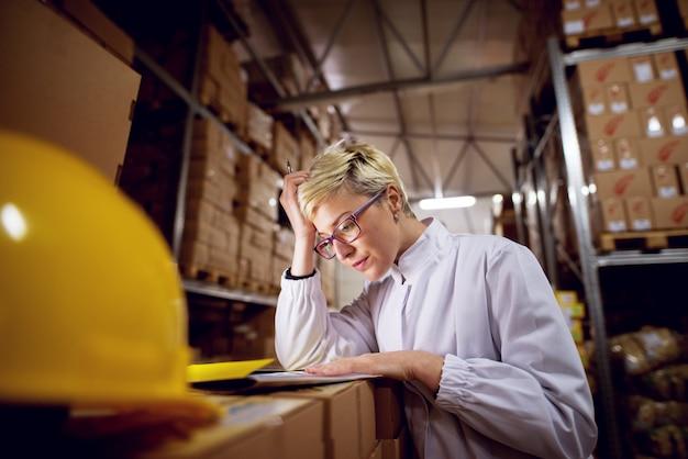 Молодой потревоженный преданный женский работник в складском помещении средства проверяет бумажные листы положенные на стоге коробок в складском помещении фабрики. Premium Фотографии