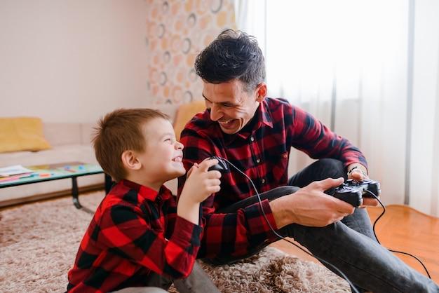 Отец и сын, сидя на полу и играть в видеоигры. веселиться и улыбаться. Premium Фотографии
