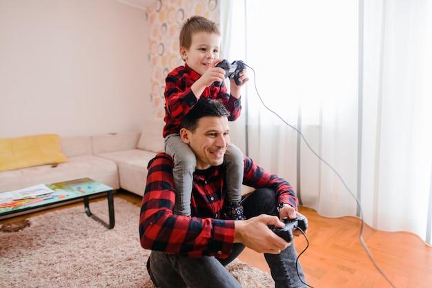День отца и сына. веселый отец и сын, играя в видеоигры. сын сидит на плечах отца. Premium Фотографии
