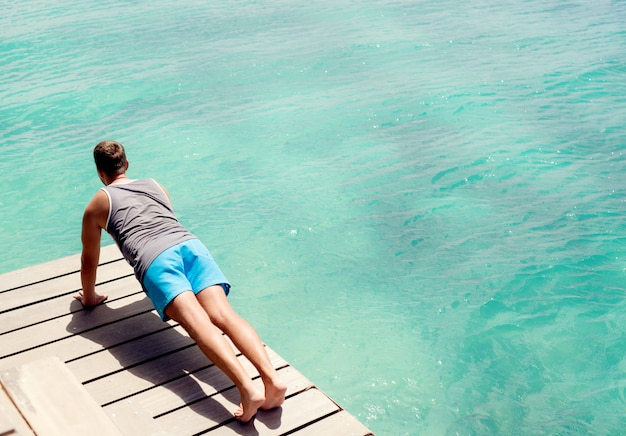 夏の屋外トレーニングを行う若い男。美しいターコイズブルーの海のそばで腕立て伏せをしています。 Premium写真