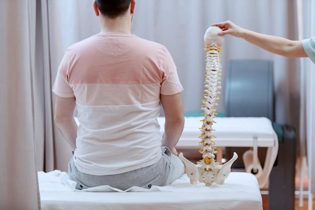 背を向けて病院のベッドに座っている男性患者。彼の隣には、脊椎モデルを保持している看護師がいます。 Premium写真
