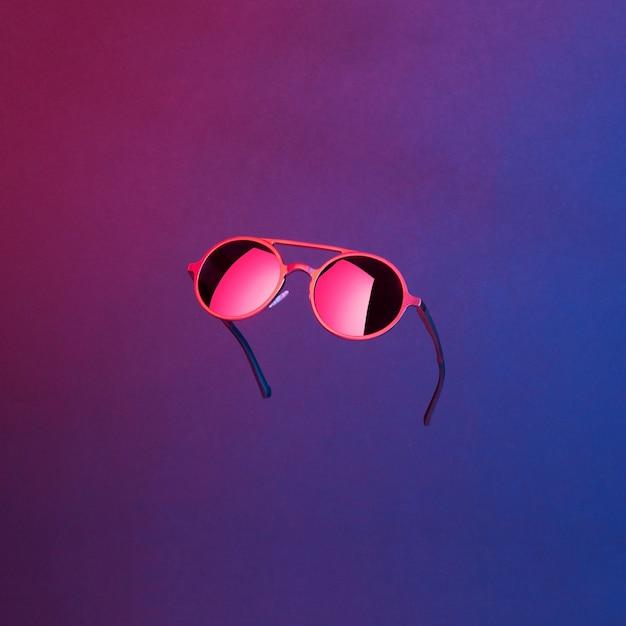 抽象的な暗い背景に浮かぶネオンの光で照らされたスタイリッシュなラウンドヴィンテージサングラス Premium写真