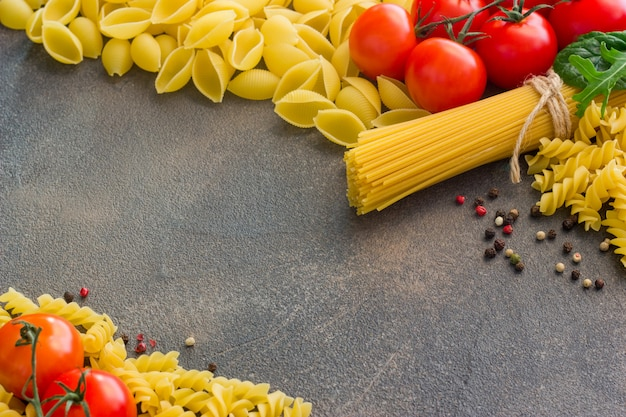 暗いテーブル、トップビューでパスタを調理するためのスパゲッティとさまざまな食材を使ったフレーム Premium写真