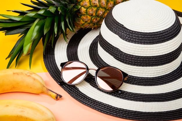 Пакет для пляжного отдыха, женские аксессуары для путешествий, солнцезащитные очки и пляжная шляпа - вкусные тропические фрукты, ананасы и бананы. Premium Фотографии