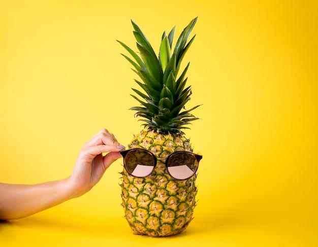 Сочный ананас с солнечными очками, концепция летних каникулов, женская рука, желтая предпосылка - питательный плодоовощ. Premium Фотографии