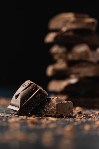 Стек из темного шоколада кусочки на темном. Premium Фотографии