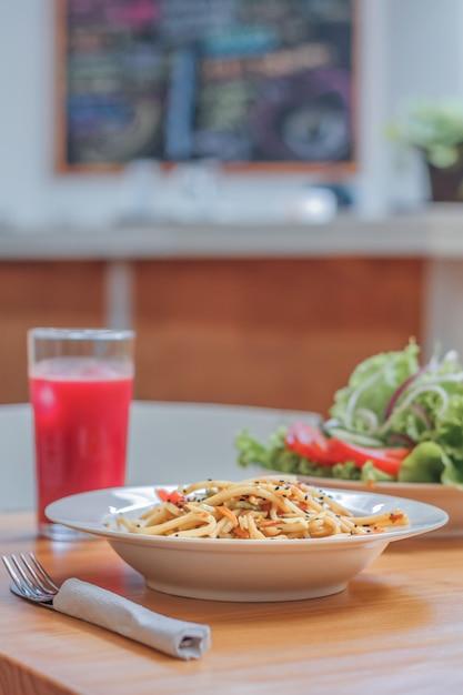 Блюдо спагетти с овощами вок и свежим салатом в ресторане. крупный план. Premium Фотографии