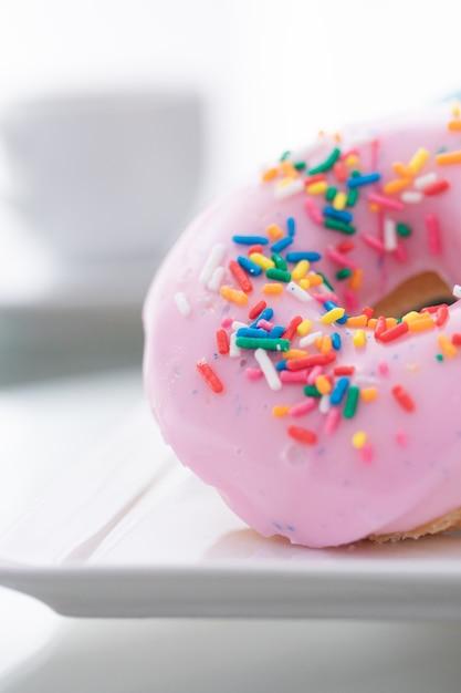 ピンク、ブルー、チョコレートが白い皿の上にドーナツを振りかけ、ライトの上に一杯のコーヒーを振りかけます。 Premium写真