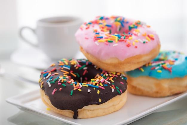 ピンク、ブルー、チョコレートが白い皿とコーヒーのカップにドーナツを振りかける Premium写真