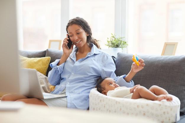 Мать, используя лотерею для ребенка во время разговора с клиентом по телефону Premium Фотографии