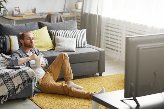 Человек смотрит телевизор в холостяцкой колодке Premium Фотографии