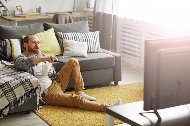 Мужчина смотрит телевизор на полу Premium Фотографии