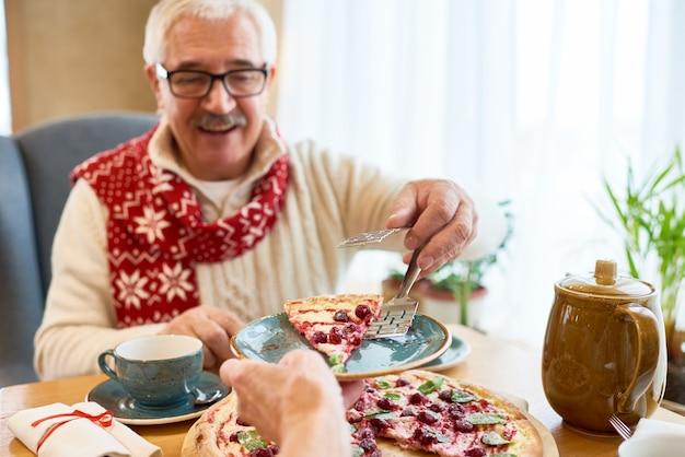 年配の男性がクリスマスディナーで甘いパイを食べる Premium写真