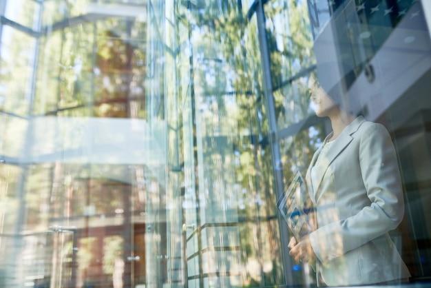 Мечтательная деловая женщина, наслаждаясь видом за окном Premium Фотографии
