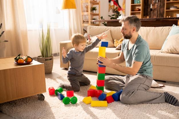 Отец помогает сыну построить башню из кубиков Premium Фотографии