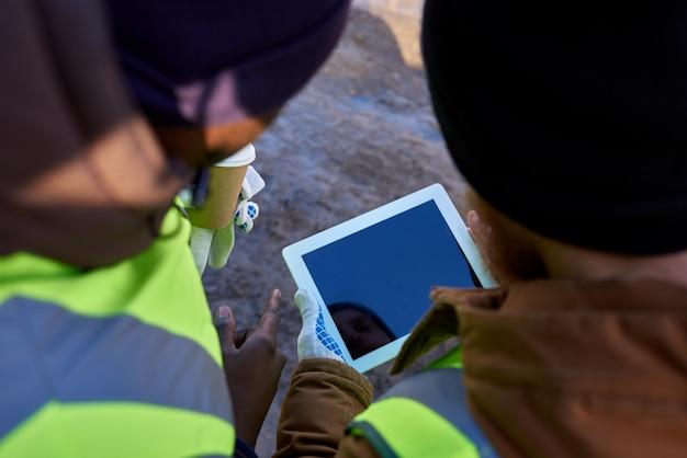 Майнеры, использующие планшет на открытом воздухе Premium Фотографии