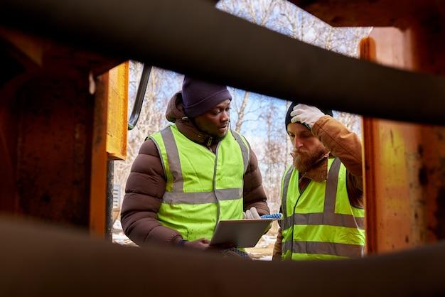 Два шахтера осматривают автомобиль Premium Фотографии