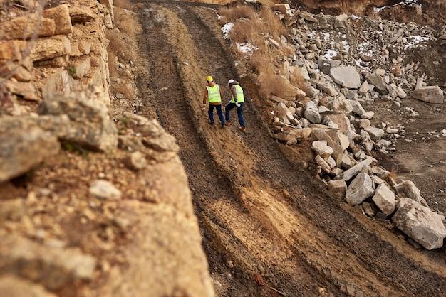 現場の土の中を歩く建設労働者 Premium写真