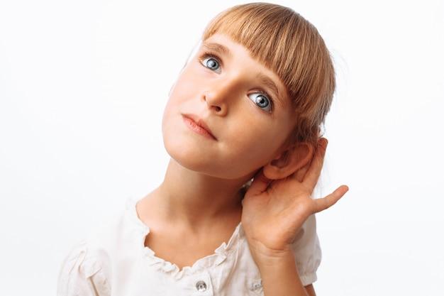Девушка слушает на белой стене Premium Фотографии