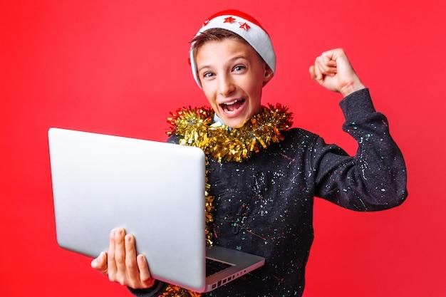 Счастливый подросток в новогодней шапке и с мишурой на шее и держа ноутбук Premium Фотографии