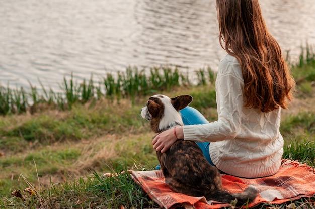 屋外の川の近くの彼女のウェールズのコーギー犬を抱き締める若い女性 Premium写真