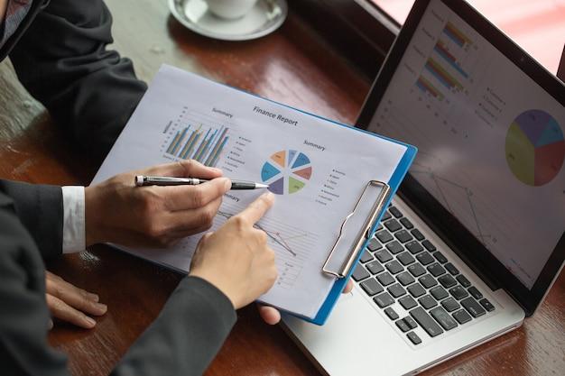 Деловой человек, анализируя финансовую статистику отображается на миллиметровой бумаге Premium Фотографии