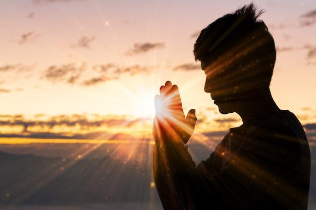 キリスト教の男の手の祈り、精神性および宗教、神に祈る人のシルエット。 Premium写真