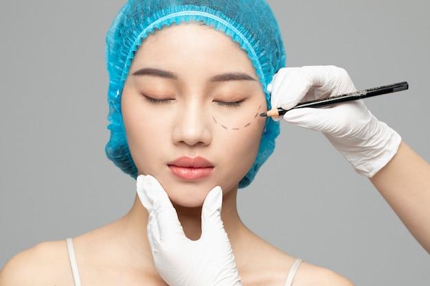 Косметолог готовит женщину к инъекции Premium Фотографии